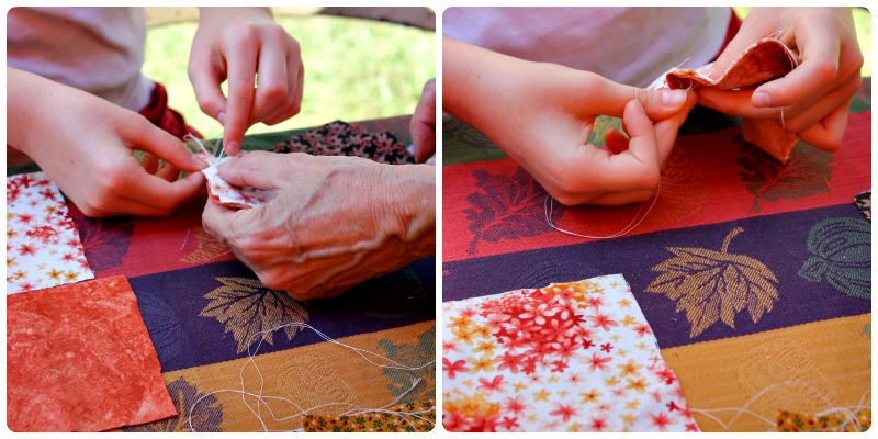 Young festival goers learning to sew a running stitch as they sewed 2 squares together
